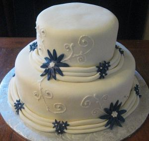 White Wedding Cake with Blue Flower Accents and Draping Fondant!